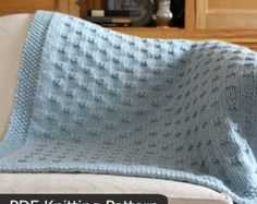 """The Third Street Blanket KNITTING PATTERN is easy to knit with super bulky weight yarn and big needles.  *********** Pattern includes directions for FIVE sizes: Approximate sizes after blocking...  = XL: 50 wide x 50.5 long = Large: 41.75 wide x 50.5 long = Medium: 38.25 wide x 38.75 long = Small (Crib/Lap): 34.5 wide x 34 long = Baby: 28.25 wide x 28 long  Any of the blanket sizes may be made longer by adding pattern repeats. Each pattern repeat adds about 1.25"""" to the length of the…"""