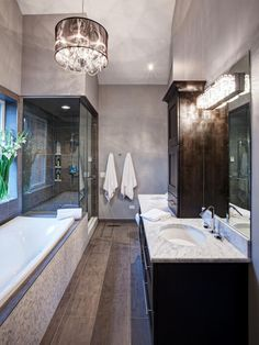 Oval under-mount sinks and polished chrome fixtures give the room a contemporary look while a drum-shaped crystal chandelier adds a sophisticated touch.