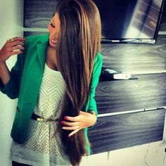 Chaqueta verde con blusa blanca estampada y minicinturón dorado ceñido a la cintura