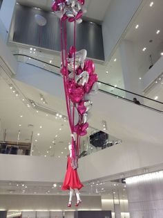 mannequin holding a balloon bouquet, as if she is floating in the store! Looks great! X