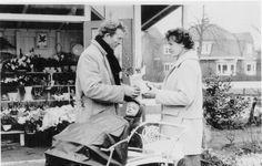Dit bloemenhuisje heeft jaren gestaan op de hoek van de Arnhemseweg en de Everhard Meysterweg. Op de foto, gemaakt in 1959, verkoopt de heer Bitterling, die in de winter ook vaak als baanveger op de ijsbaan aan de Rubensstraat te vinden was, een bloemetje aan mevrouw. F. van Dijken-Sickman. Haar oudste zoontje kijkt belangstellend toe.