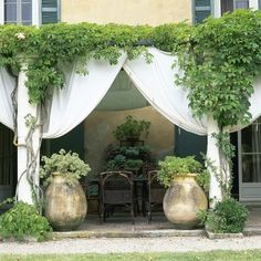 Patio Country Patio Vine-covered patio dining area with draped fabric, columns and potted plants.Country Patio Vine-covered patio dining area with draped fabric, columns and potted plants. Patio Dining, Outdoor Dining, Dining Area, Rustic Outdoor, Patio Chairs, Outdoor Rooms, Outdoor Gardens, Country Patio, Country Porches