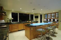 Kitchen remodel done by us. By combining glass countertops and LED lighting, ThinkGlass has created countertops that literally glow, creating an ambiance appropriate for both indoor and outdoor applications. View from the other end.
