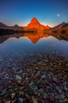 Two Medicine Lake, Glacier National Park, Montana - We drove early morning from St. Mary's Lodge to see the sunrise at Two Medicine lake in Glacier National Park. There were no clouds but the lake water was so calm, it created perfect reflection of the red light kissing the Sinopah Mountain. As there was no wind in the morning, the colorful rocks in the foreground were visible.