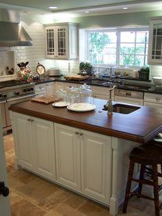island w/ wood counter, cabinets w/ black counters, white subway tile