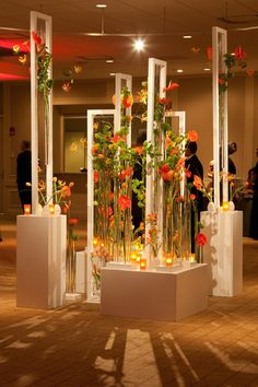 We are absolutely crazy about this idea of combining linear objects with lovely flowers to create this installation. This could be a great focal point for the center of the room and can match the corporate colors.