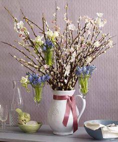 Поставьте в кувшин вербу с почками и искусственные цветущие веточки. А затем с помощью проволоки подвесьте крошечные вазочки (или пробирки) с маленькими весенними цветочками, например, мускари.  Завершите эту праздничную композицию нарядной шелковой лентой, обвязанной вокруг горлышка кувшина. Цвет ленты выбирайте в гармонии с оттенками букета.