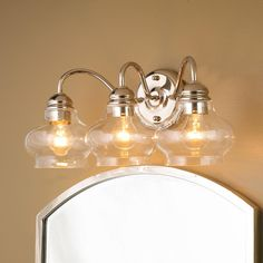 """Clear Cloche Glass Bath Light- 3 Light  Clearly stylish with shapely onion glass globes and polished nickel or bronze hardware for a look that goes traditional to modern! 3x60 watts (medium base sockets) (10""""Hx20""""Wx9""""D)"""