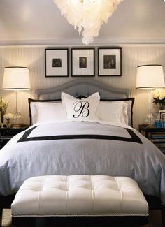 this bed looks blissfully comfy... maybe a little too comfy, which would make me never want to leave it. loving the padded headboard with the rivets and the chandelier. all in all, clean, peaceful, bliss.