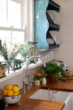 blue spatter-painted hanging dish rack, butcher-block counter top, wide windowsill/shelf notched out to fit a pot filler faucet - great design!