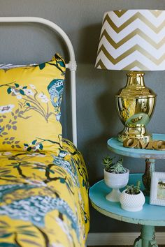 DwellStudio bedding styled with a gold lamp and small succulent planters