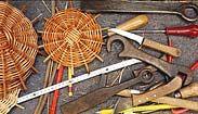 Arrangement von einigen Korbböden mit Werkzeugen eines Korbmachers.