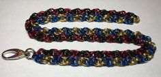 Spiral weave chainmaille lanyard - created on commission for a World of Warcraft fan! One strand is the colors of the Horde (red/black) and the other is the colors of the Alliance (blue/gold). For the bi-factional player in all of us. :)