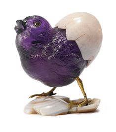 A FRENCH GOLD, HARDSTONE AND GEM-SET MODEL OF A HATCHING CHICK, PURCHASED BY GRAND DUKE ALEXI ALEXANDROVITCH, MAISON CARTIER, PARIS, 1907. finely carved of solid Amethyst with ruffled feathers emerging from a chalcedony cracked shell, realistically chased gold feet standing on broken eggshell base, with faceted gem set eyes the bar engraved with inventory number 506. | sotheby's