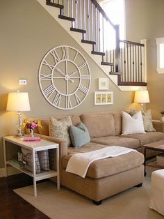 ideas to decorate with a large clock in a living room above the couch on the back of the stairwell wall. Slightly country decor