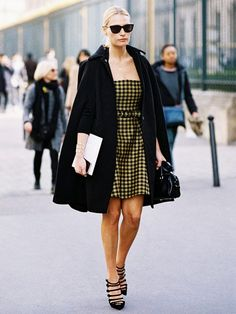 A gingham mini dress is worn with a black cape and strappy pumps