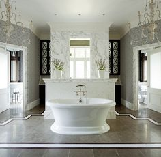 Totally his and hers master bathroom with separate toilet rooms and sinks behind the tub wall   fantastic boarder on floor