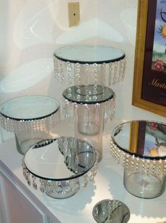 looks like they used dollar store vases and attached mirrors to the top then the jewels. I would spray paint cheap candlesticks silver and place in between the mirrors to create a cupcake stand - Crafts Are Fun Dollar Store Crafts, Dollar Stores, Thrift Stores, Bolo Diy, Diy Centerpieces, Centrepieces, Dollar Tree Centerpieces, Bling Centerpiece, Candy Table