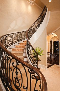Spectacular curved staircase of wrought iron railings and solid wood top