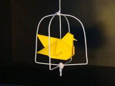 móbile de gaiolinha com passarinho de origami em papel importado, arame decorado branco, fio branco de aprox. 45 cm e caixa em origami, papel kraft 180-200 g/m². medida aprox. do passarinho é de 7x5 cm e da embalagem é de 10x10x9,5cm Outras cores disponíveis: Branco, azul, bordô e vermelho. R$ 42,00