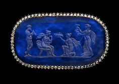 Gold and silver brooch, the rectangular frame set with a continuous line of diamonds surrounding a sapphire intaglio representing a celebration. A woman in drapery seated on a throne is welcoming two women similarly draped, one kneeling before her offers a bowl full of fruit, the other holds up a wine cup, to the sound of music played by a man standing behind the throne. Intaglio, late 18th century - 19th century, setting modern.