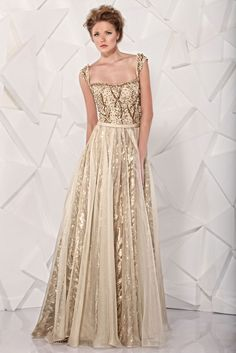 TONY WARD - Gold evening dress featuring a bodice embroidered with crystals and silk and a skirt in sequins covered by gazar.