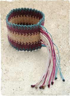 Woven of waxed cotton in fresh shades of turquoise, berry and taupe, our wide cuff is finished with a boho-chic, beaded fringe closure.