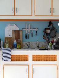 Orange and Blue kitchen.  Love the simple line for the cupboard!