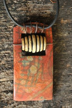 Page McNall ... A thick polymer clay pendant accented by a white horn bead. The nitrile (non-latex) cord is trapped in place with antiqued copper wire.