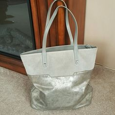 """Stella & Dot Hudson Tote Medium From current Spring book.  Slate gray perf. Detail  and brushed Metallic tote. I carried this bag for a few  months but still in excellent condition.  Only issue is small wear on handle.  See 4th pic. 13 1/2"""" H X 12 1/4"""" L X 5 1/2 """" D X 9"""" strap drop. I received  tons of complements on this! Stella & Dot Bags Totes"""