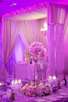 Fuchsia uplights illuminate this beautifully draped wedding venue canopy