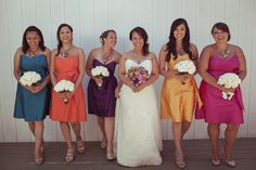 I like the multi-color bridesmaid dresses, but with vibrant flowers bringing them all together.