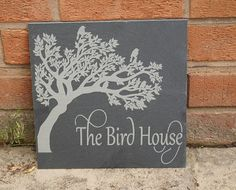Add a rustic feel to your garden or house with the inclusion of a slate house sign. This sign features a tree with birds perched in the branches.  All signs are pre-drilled to your requirements either to allow you to hang the sign via a jute twine or pre-drilled at the sides to allow you to screw the sign into the wall. Size 32 x 26cm  Made from natural Welsh slate these signs are protected with a oil that protects and adds a sheen to the surface. Our slate has protective foam pads to the…