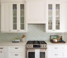 white kitchen with Caesarstone Frosty Carrina countertops, gas range, arabesque tile backsplash, chicken wire cabinet fronts, cup pulls, built in vent hood