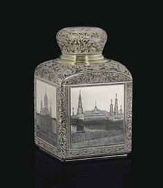A SILVER & NIELLO TEA CADDY -   MAKER'S MARK OF MARIA SEMENOVA, MOSCOW, 1899-1908 -   Rectangular with slightly rounded corners, sides with cartouches depicting nielloed views of Moscow landmarks, within borders decorated with foliate arabesques in the Old Russian style, the baluster cover enclosing a gilt stopper and nielloed with similar arabesques, marked throughout  5¼ in. (13.3 cm.) high