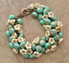 A Rustic Bracelet Reminiscent of the Southwest has Turquoise Colored and Bell Flower Shaped Glass Beads