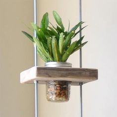 Make this vertical planter using blocks of reclaimed wood, threaded rods and nuts, and some recycled food jars or mason jars.