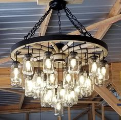 A Wagon Wheel Chandelier with a mix of rustic/vintage features and finishing techniques creating a unique handcrafted chandelier - Beleuchtung Ceiling Canopy, Ceiling Lights, Wagon Wheel Chandelier, Wagon Wheel Light, Wagon Wheel Decor, Mason Jar Chandelier, Steel Rims, Electrical Tape, Lamp Socket