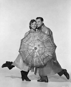 Full publicity shot of Debbie Reynolds as Kathy Selden and Gene Kelly as Don Lockwood wearing raincoats and hats, holding umbrella.