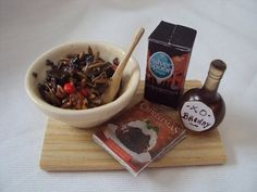 DOLLS HOUSE MINIATURES MAKING THE CHRISTMAS PUDDING BOARD SET WITH BOWL OF PUDDING MIX, BRANDY, SUGAR AND BOOK