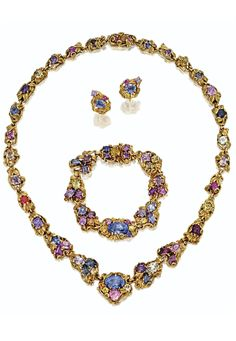 Tiffany & Co., designed by Louis Comfort Tiffany, circa 1910. Comprising a necklace, a bracelet and a pair of earrings, formed of sculpted gold links of foliate and scroll design, set with a variety of coloured stones, including sapphires in multiple hues