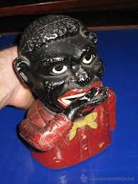 Metal golliwog money box where you placed the coin on his hand before pushing the little lever down at the back, which caused his hand to rise up to his mouth. The coin then slides down his throat.