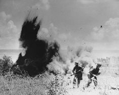 July 1944: U.S. Marines walk away from a Japanese foxhole after blowing it up with explosives, during the invasion at Saipan, in the Mariana Islands.