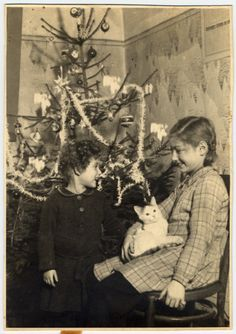 Halina and Eva Litman stand pose next to a Christmas tree while in hiding in Tluste in a washer woman's house.