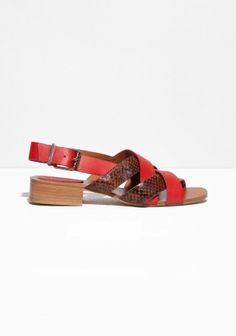 Contrasting cross-crossing straps detail these supple leather sandals featuring a buckled sling-back strap, all atop a comfortable stacked block heel.