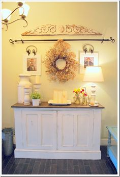 Love this idea! The Curtain Rod, Wreath, and Two small pictures.....Right behind the front door since it only get's used when we have company.  No cabinet.