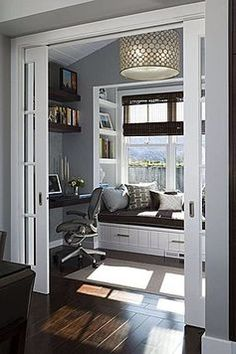 Great contemporary gray and white home office design with hardwood floors, big bay window seat.