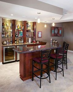 Traditional L-shaped basement bar with high countertop installed. Stained maple wood with black granite and steel bar stools tie this area together.
