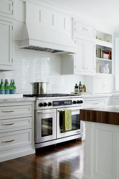 white cabinets and white subway tile; white marble counter w/grey veins and butcher block island countertop