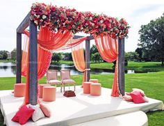 A steel framed canopy or mandap is draped with peach, pink and coral fabric and flowers for an outdoor Indian wedding by HMR Designs